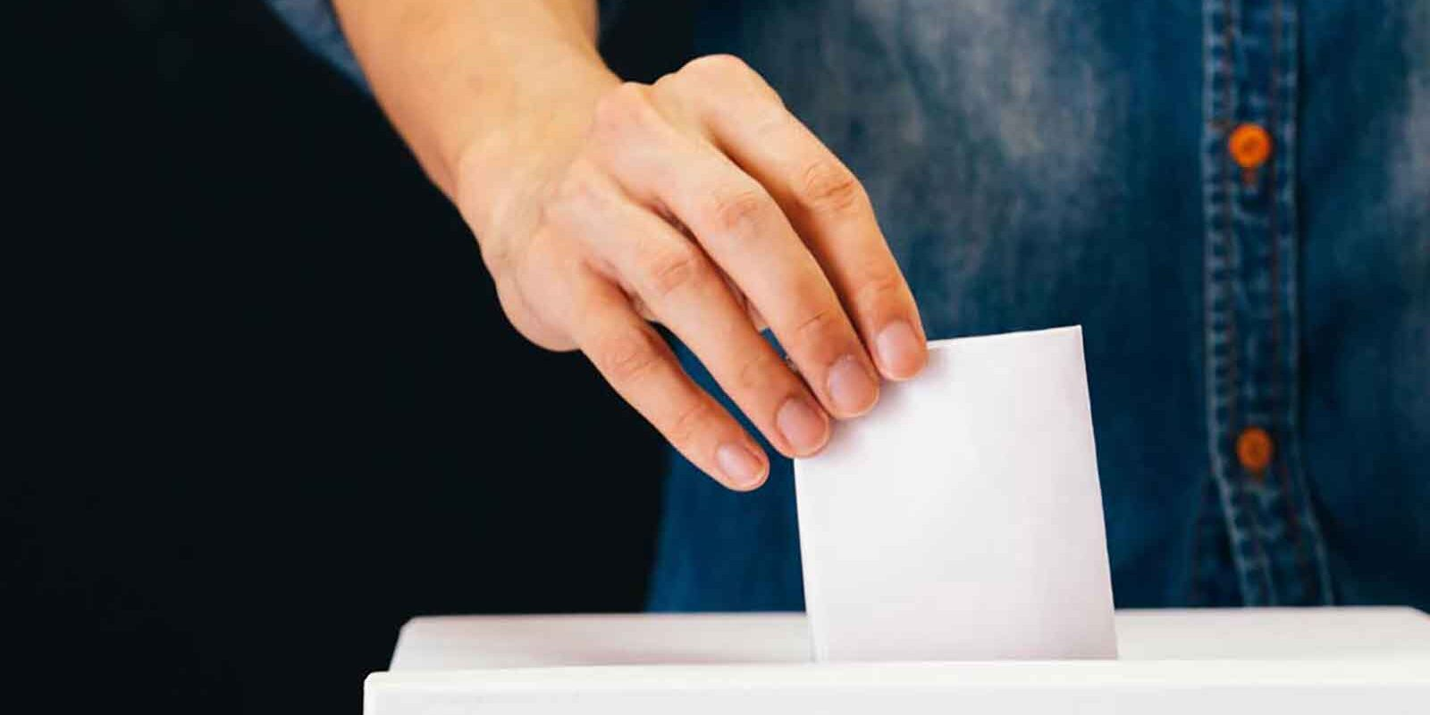 Hand putting ballot in ballot box
