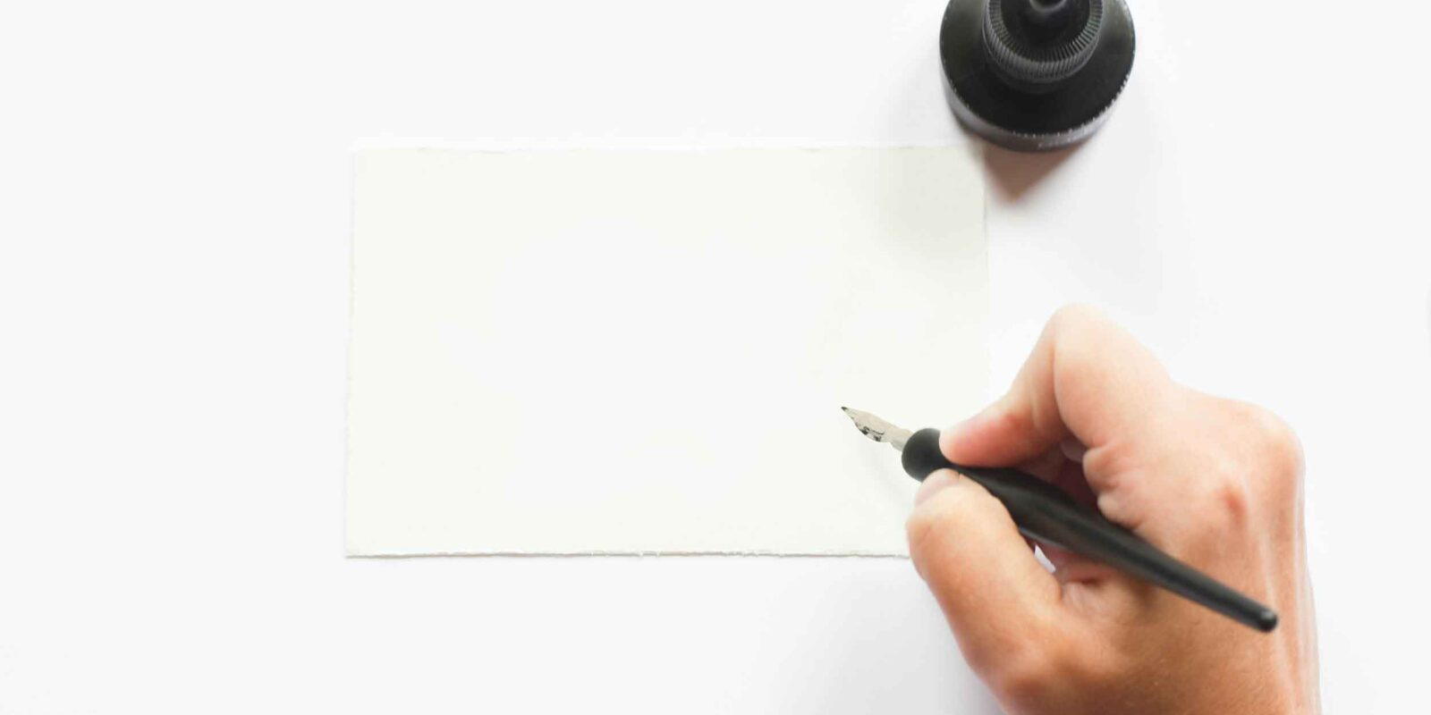 Hand holding pen over a blank sheet of paper